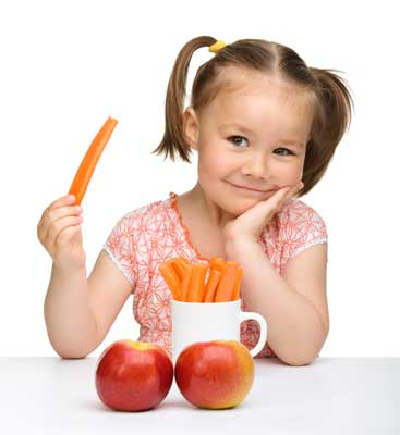 young girl with pigtails holding carrot