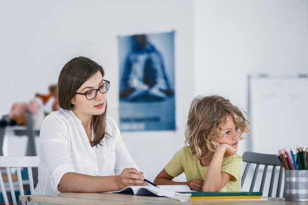 Young female tutor with ADHD boy student