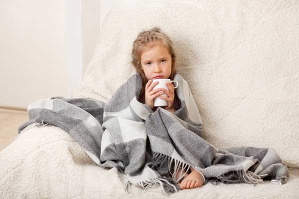 young girl wrapped in blanket with coffee mug
